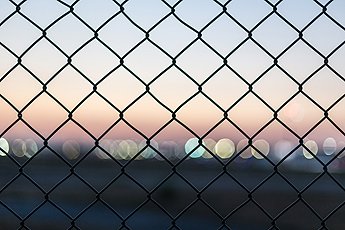Commercial Fencing with city lights at dusk in the background