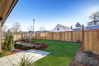 Tall wood fence made by Fence Companies in Arlington Heights IL, enclosing a backyard