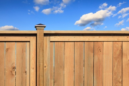 A cedar fence in Joliet with a blue and cloudy sky in the background